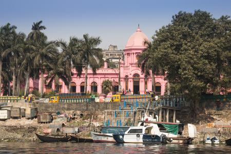 DHAKA, BANGLADESH - FEBRUARY 2017: The pink palace of Ashan Manjil seen from the river in Sadarghat, the old center of Dhaka in Bangladesh