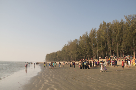 COXS BAZAR, BANGLADESH - FEBRUARY 2017: People on the longest beach in the world in Coxs Bazar in Bangladesh