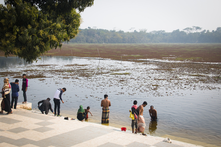 BAGERHAT, BANGLADESH - FEBRUARY 2017: People bathing in the big lake at the Tomb Mosque of Khan Jahan Ali in Bagerhatat the edge of the Sundarbans in Bangladesh Editorial