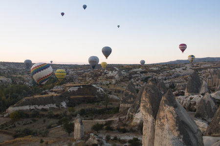 GOREME, TURKEY - OCTOBER 2017: Many hot air balloons fly every morning with tourists over Cappadocia in Turkey