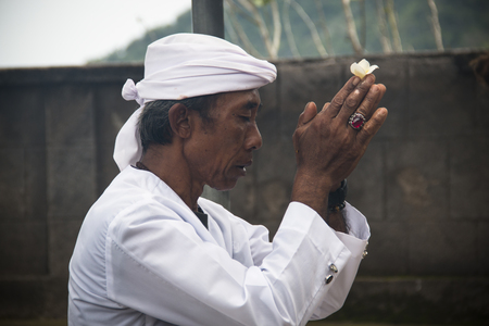 PEMUTERAN, BALI - JANUARY 2018: A hindu priest performing offerings in a temple in Pemuteran in Bali, Indonesia Фото со стока - 120168038