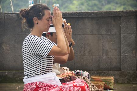 PEMUTERAN, BALI - JANUARY 2018: A hindu priest performing offerings in a temple in Pemuteran in Bali, Indonesia Фото со стока - 120168039