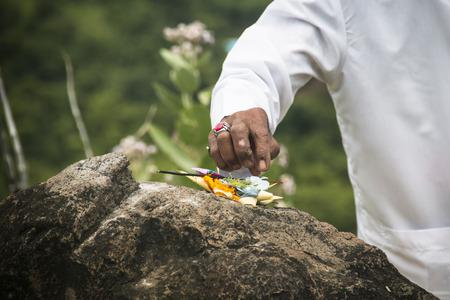 A hindu priest performing offerings in a temple in Pemuteran in Bali, Indonesia Imagens