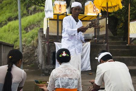 PEMUTERAN, BALI - JANUARY 2018: A hindu priest performing offerings in a temple in Pemuteran in Bali, Indonesia Редакционное