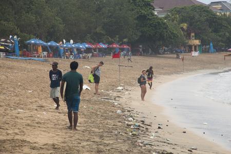 KUTA, BALI - JANUARY 2018: People and lots of garbage on Kuta beach in the south of Bali island in Indonesia Фото со стока - 120168012