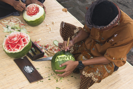 PEMUTERAN, BALI - JANUARY 2018: Watermelon carving is a very precise art performed by men in Bali, Indonesia Фото со стока - 120168004