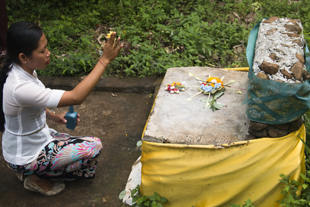 PEMUTERAN, BALI - JANUARY 2018: A group of women in Bali, Indonesia preparing the daily offerings with food and flowers
