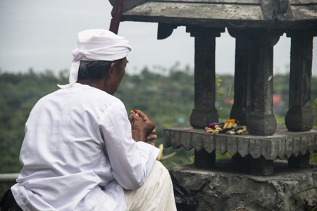 PEMUTERAN, BALI - JANUARY 2018: A hindu priest performing offerings in a temple in Pemuteran in Bali, Indonesia Редакционное