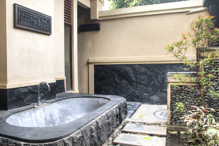 Outdoor bathroom with stone bath in a fancy hotel in Pemuteran in Bali, Indonesia Редакционное
