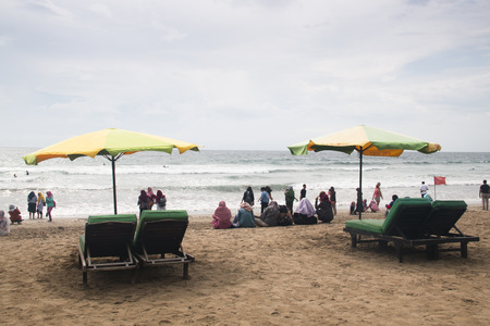 KUTA, BALI - JANUARY 2018: People and lots of garbage on Kuta beach in the south of Bali island in Indonesia