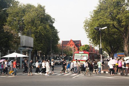 BANGKOK, THAILAND - FEBRUARY 2018: A group of Asian tourists crossing the road in the center of Bangkok, the capital of Thailand