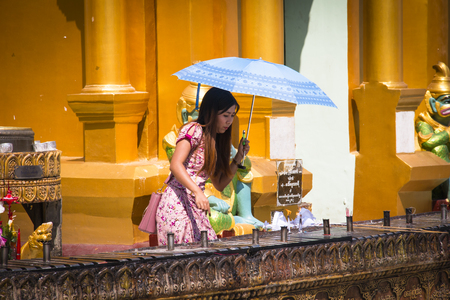 YANGON, MYANMAR – MARCH 2018: The impressive golden Shwedagon Pagoda is one of the most famous temples in Yangon, the capital of Myanmar Фото со стока - 120168071