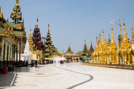 YANGON, MYANMAR – MARCH 2018: The impressive golden Shwedagon Pagoda is one of the most famous temples in Yangon, the capital of Myanmar Фото со стока - 120168072