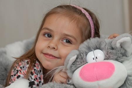 Petite fille embrassant jouet pour chat doux