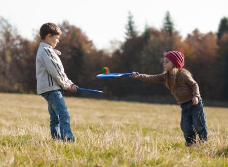 Enfants jouant au tennis sur la pelouse en face de la forêt