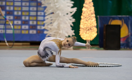 Girl doing split with hoola hoop. Gimnastics open tournament. 16-17th December 2011, Lviv, Ukraine