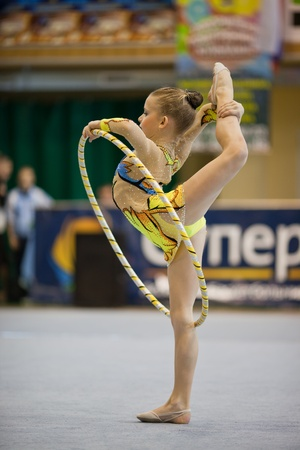 Girl doing vertical split with hoola hoop. Gimnastics open tournament. 16-17th December 2011, Lviv, Ukraine