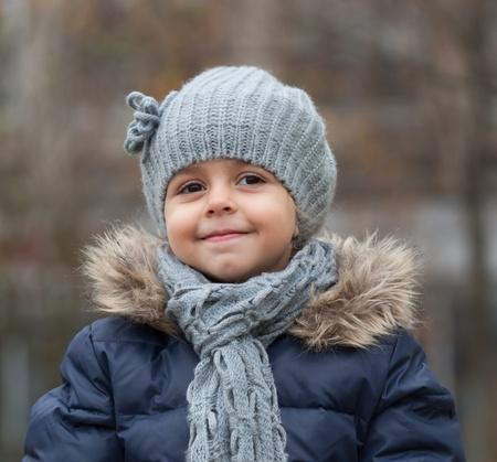Portrait de sourire petite fille avec le chapeau et l'écharpe en tricot. Banque d'images