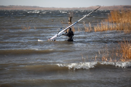 dry suit: Windsurfer in a dry suit is going through the problematic cane and woody area to set off in the high wind zone