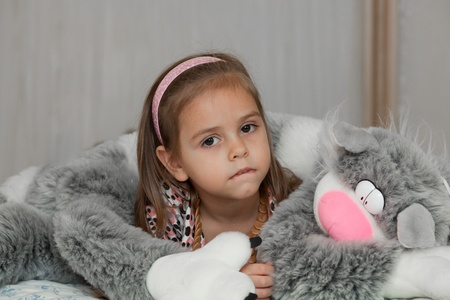 Little girl in the embraces of cat soft toy
