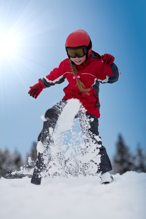 Young girl skier throwing up snow flakes with her ski