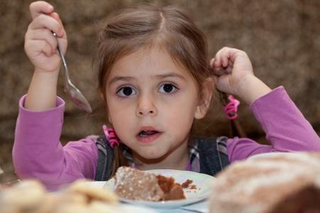 Look of little girl eating cake dessert