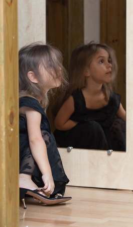 Little girl in mother's little black dress and mother's shoes. Reflection in the mirror. Stock Photo - 11850767