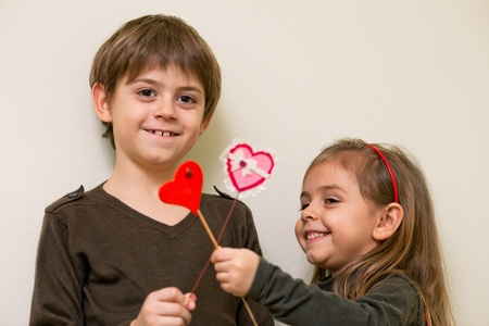 Boy gives heart to little girl  and little girl  gives heart to boy photo