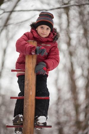 ni�o escalando: Muchacho joven que juega al aire libre en el parque de invierno. Foto de archivo