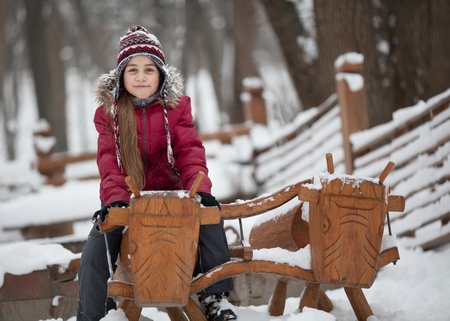 preadolescent: A caucasian 9 years old girl at woody playground. Pre-adolescent girl sitting on woody cow. Stock Photo