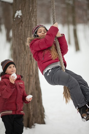 Preadolescent girl and boy have fun with snowball and rope outdoors photo
