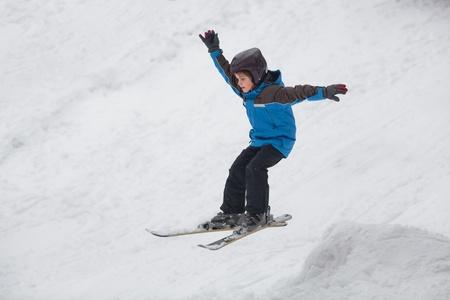 Petit garçon de sauter sur les skis alpins Banque d'images