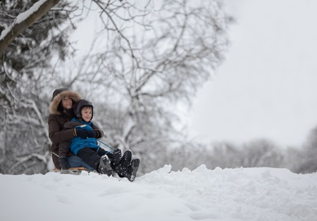 pre adult: Mother and son preparing to go down the slope on sledge