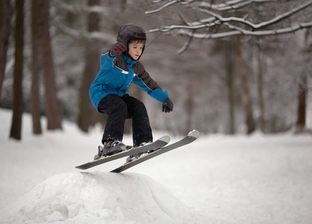 Little boy jumping on downhill skis photo