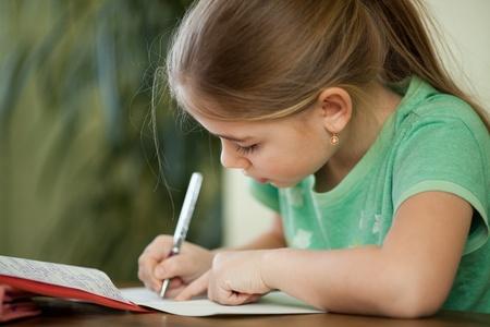 persona escribiendo: Chica hace los deberes en su cuaderno. Foto de archivo