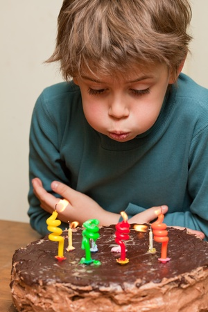 8 years birthday: Young boy blowing out candles on a birthday cake Stock Photo