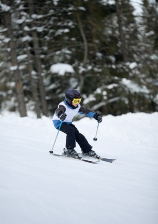 Young skier at downhill slalom competitions photo