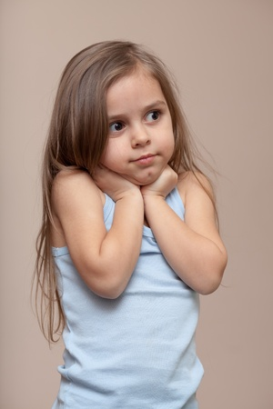 females only: Beautiful little girl holds her hands up against her neck