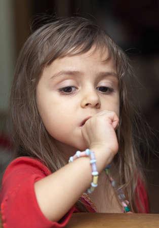 Portrait d'une petite fille sérieuse dans les bijoux en plastique Banque d'images