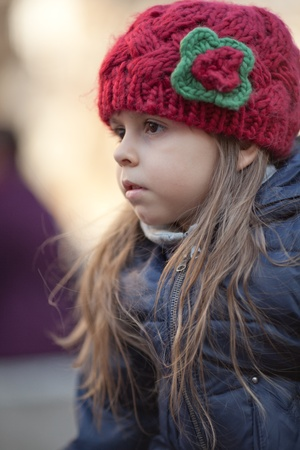 sullen: Portrait of serious little girl in red knitted hat