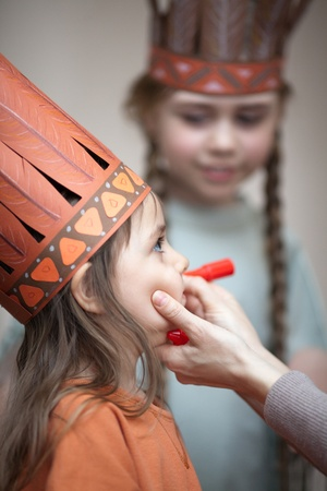 Two sisters dressed as Indians. Mother painting face of her daughter photo