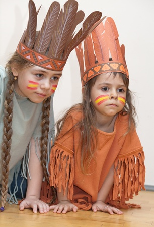 Two sisters dressed as Indians on the floor Фото со стока