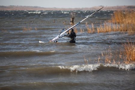 dry suit: Windsurfer in a dry suit is going through the problematic cane and woody area to set off to high wind zone Stock Photo