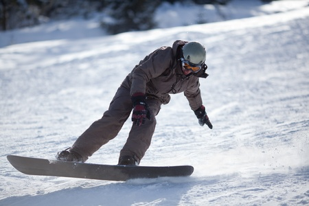 Man snowboarding down the slope going to stop photo