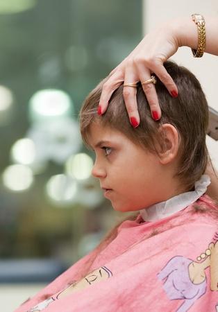 Boy getting a haircut at barber shop photo