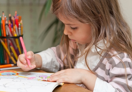 Sweet little girl sitting at desk and paints with a color pencil  Stock Photo