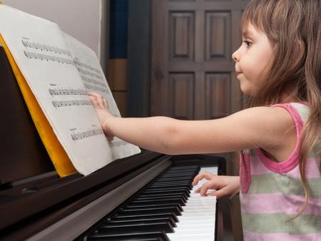 Petite fille essayant de lire des notes de piano et de jouer Banque d'images