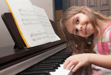 Little girl smiling at piano keyboard photo