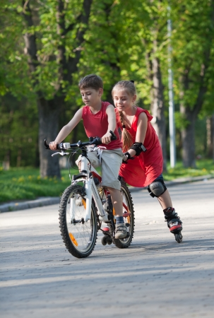 Beautiful little girl on   in-line skates following little boy on bicycle in a park at summer afternoon Фото со стока