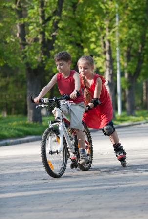 Belle petite fille sur patins à roues alignées à la suite petit garçon à vélo dans un parc à l'après-midi d'été Banque d'images